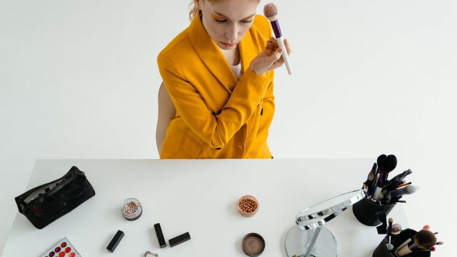 woman in yellow blazer holding makeup brush